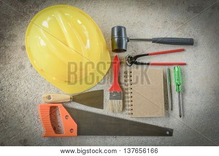 paint brush,Plastering trowel, hammer, screwdriver,Cream wire cutters, saws,notebook,pen on the cement floor
