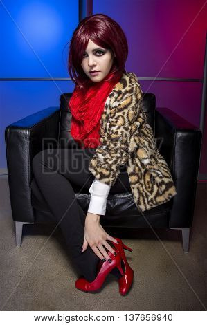 Young fashionable female in a colorful nightclub wearing red high heel shoes