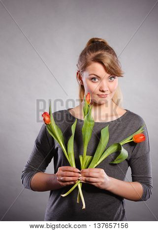 People and flowers. Girl love nature holding red green tulip spring flower. Woman adoring natural environment.