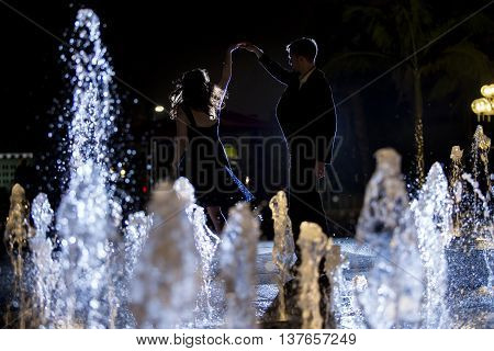 Engaged interracial couple on a romantic date at night on a city fountain