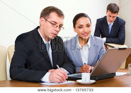 young businesswoman looking at the monitor of laptop placed on the table and businessman writing notes sitting near by her and young reading man on the background