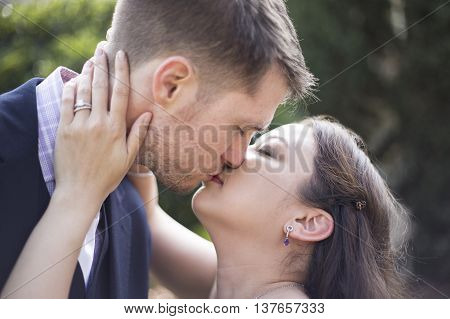 Close up of romantic engaged Caucasian and Asian couple kissing with engagement ring
