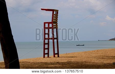 red wooden lifeguard stand on beach sand, palm tree trunk in foreground, Thai longtail boat in background, Thailand