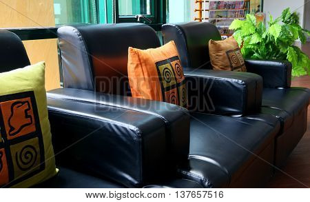 side-lit black faux-leather armchairs in front of large window, with colorful orange and yellow pillows, green plant, blue curtain
