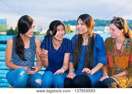 Four young women sitting together enjoying time at lake talking.