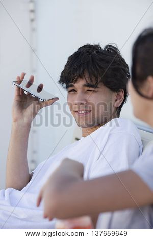 Young handsome biracial young man smiling relaxing in white tshirt tablet in hand