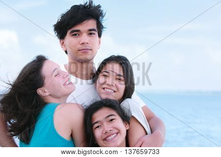 Tall young biracial man hugging three laughing young women outside with ocean horizon in background