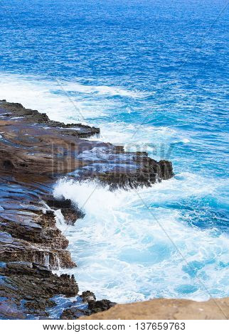 Beautiful tropical blue ocean water hitting against rocky edge along Hawaii's coast