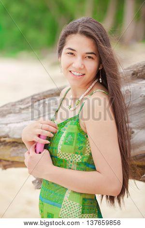 Beautiful biracial Asian Caucasian teen girl holding cellphone smiling on Hawaiian beach profile to camera