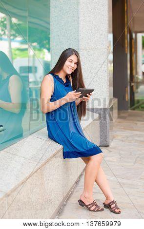 Beautiful biracial Asian Caucasian teen girl holding tablet computer sitting outside store window
