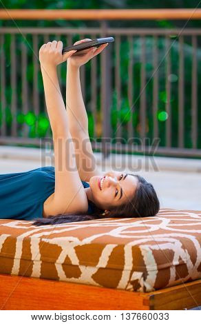 Beautiful biracial Asian Caucasian teen girl lying on outdoor bench using tablet computer