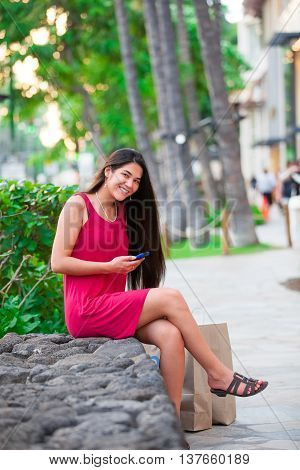 Beautiful biracial Asian Caucasian teen in red dress with cellphone sitting in Hawaii with palm trees and shopping area in background
