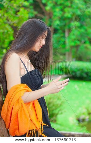 Beautiful biracial Asian Caucasian teen girl using cellphone with greenery in background side profile