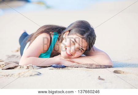Beautiful biracial Asian Caucasian teen girl lying on sandy beach resting and smiling