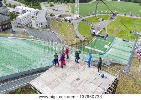 LILLEHAMMER, NORWAY - JUNE 27: Advantage of the beautiful weather, tourists visit the ski jump on June 27, 2016 in Lillehammer, Norway. Lillehammer is the center of winter sports.