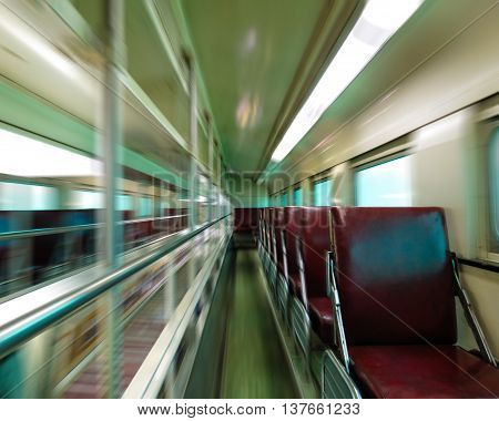 Empty passenger train car with motion blur and one seat in focus