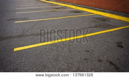 An empty parking spot with yellow lines beside the building