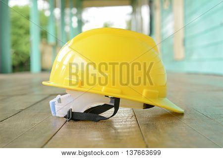 yellow helmet placed on old wooden floor