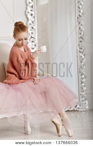 Pretty young ballerina drinks coffee. Ballerina in tutu and pink sweater