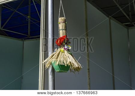 Birdhouse with grass and other material and hanging from roof.