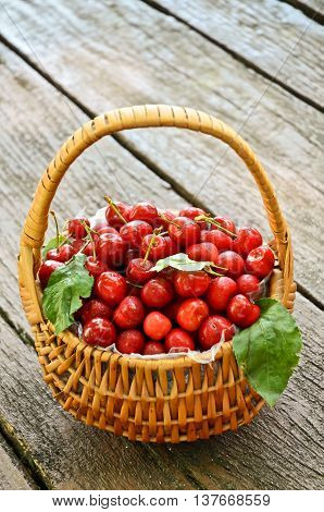 Sweet cherries in the basket on rustic table