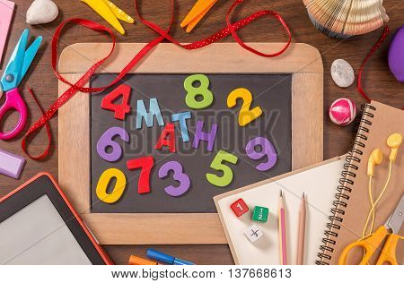Math word formed by color wooden alphabets on small blackboard with school supplies on wooden table