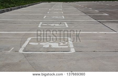 Several Parking spaces specifically for disabled people. White signs on gray concrete area.