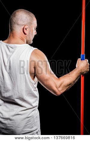Rear view of athlete standing with javelin on black background