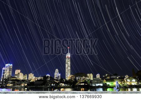 Gold Coast Surfers paradise cityscape and Q1 star trails astro with person sitting in foreground admiring the view