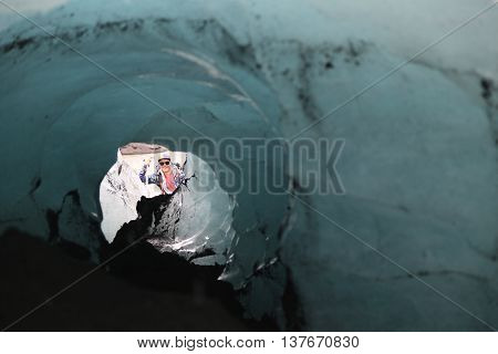 ICELAND - JULY 4, 2016: Tour guide exploring ice cave at Solheimajokull glacier. Solheimajokull glacier is one of the biggest glaciers in Europe