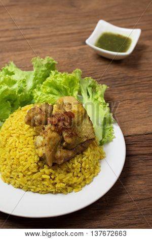 Thai chicken biryani (Khao Mok Gai) or Yellow curry rice Thai Food Style on wood background
