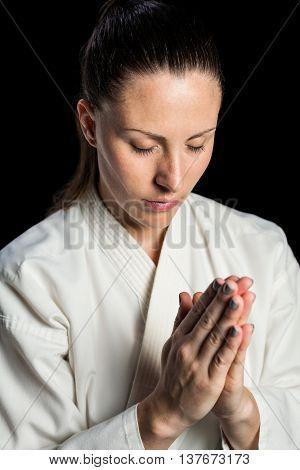 Close-up of karate fighter meditating on black background