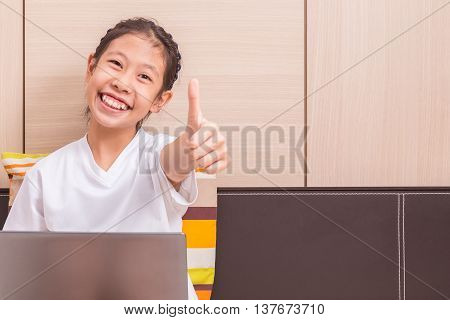 Happy smiling asian girl using notebook computer to study in her bedroom reaching out her hand to give thumb up to camera room for copy space text