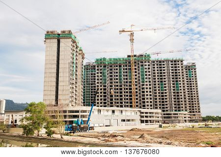 The technology or art of high rise apartment construction using crane, lift, metal beam, brick, metal ladder and concrete in construction site.