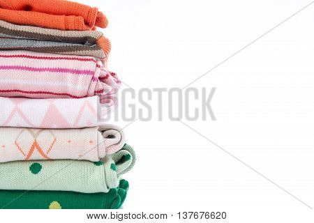 Stack of colorful cozy knitted sweaters on white background with copy space