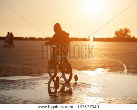 child rides a bicycle through a puddle on the background of the setting sun