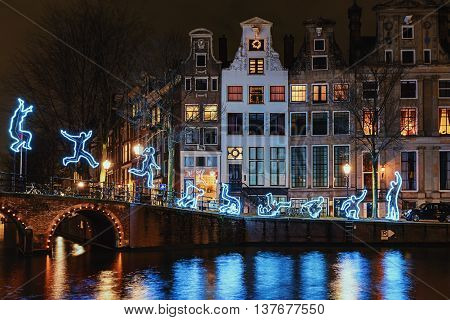 Amsterdam Netherlands - December 18 2015: Light Festival Amsterdam a light figure makes a somersault with as decor Amsterdam Canal Houses and bridge