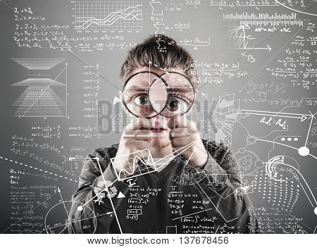 young man look through two magnifying glasses to mathematical formulas and problems.