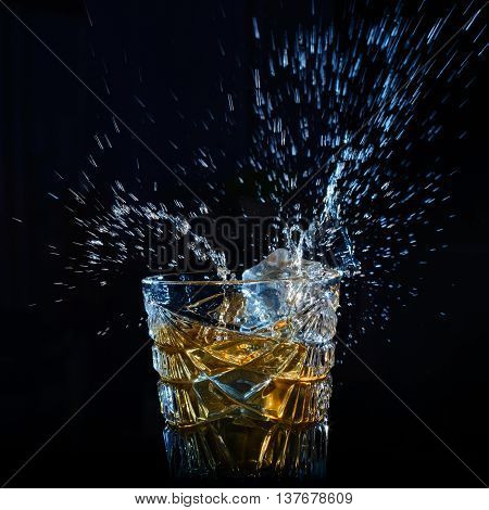 whiskey splash from the falling ice cubes in faceted crystal glass isolated on a black background