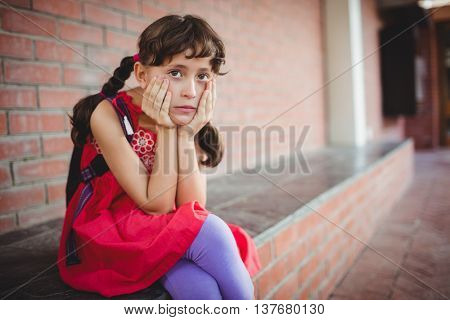 Girl holding her cheek with a desperate looking