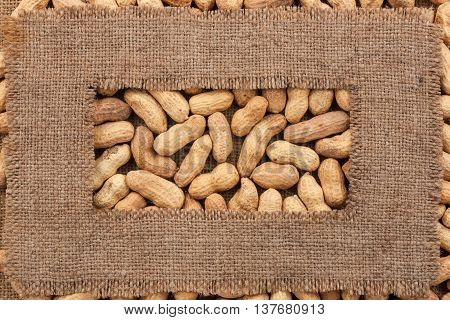 Frame made of rough burlap lies on peanuts as background