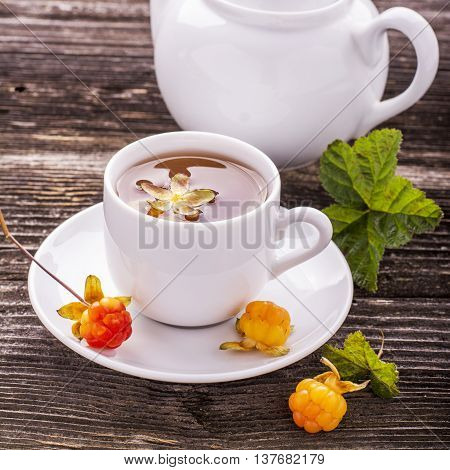 Useful light breakfast snack. Fresh herbal fruit tea with berries and leaves north cloudberries in a white ceramic cup on a dark wooden background. Rare very useful berry, called the king.