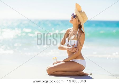 Happy young woman applying sunscreen on her hand