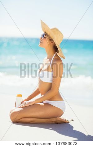 Attractive woman with sunscreen lotion taking sunbath on beach