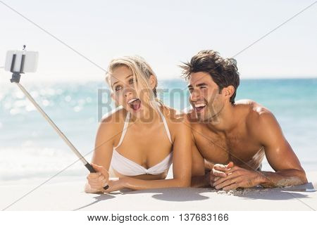 Young couple taking selfie with selfie stick on beach