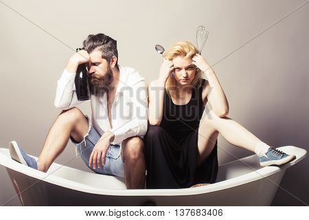 young family couple of blonde pretty girl with kitchen utensils and bearded man with long beard holding wine bottle sitting on bathtub. household everyday life and routine