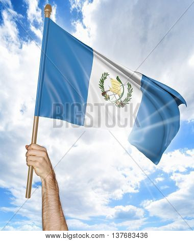 Person's hand holding the Guatemalan national flag and waving it in the sky, 3D rendering
