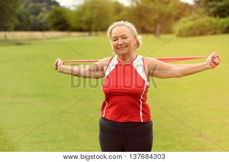Fit Senior Woman Using Resistance Bands Outside