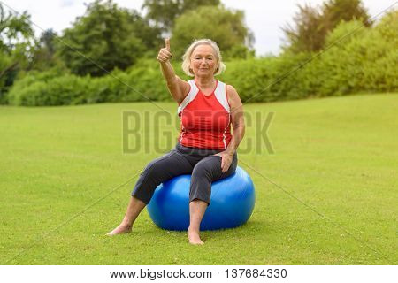 Woman Seated On Stability Ball With Thumb Up