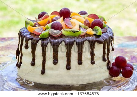 Tasty cake decorated with chocolate glaze and fruits